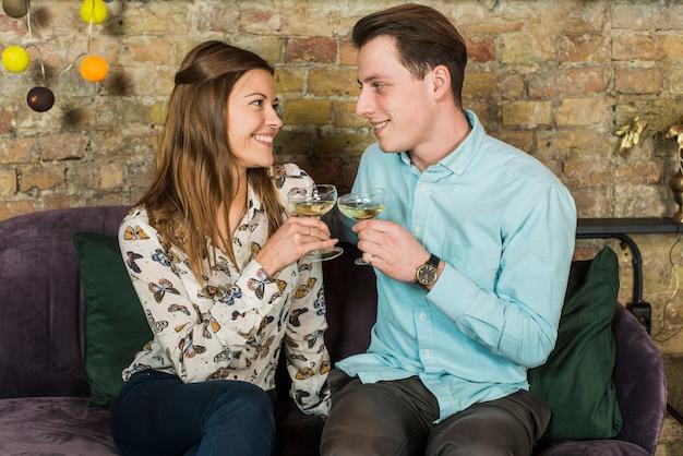 Sorridente giovane coppia tostatura bicchieri di vino nel club