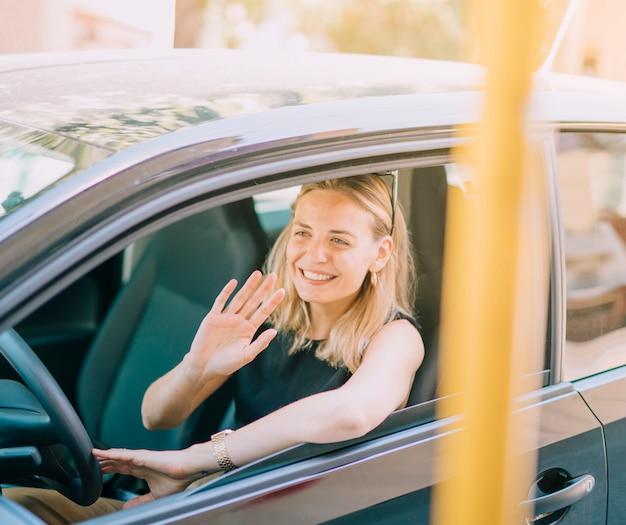Sorridente giovane donna bionda che guida l'auto agitando la mano