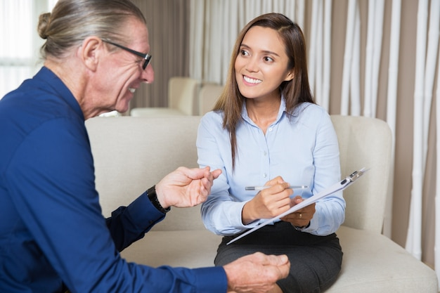 Sorridente giovane donna che chiede man domande anziani