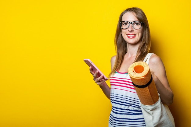 Sorridente giovane donna con telefono e karimat in borsa su sfondo giallo.