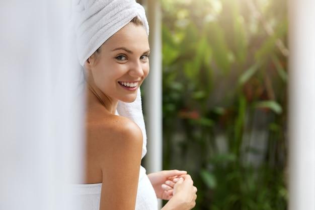 Sorridente giovane donna in asciugamani