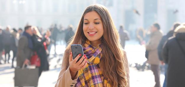 Sorridente giovane donna leggendo i messaggi sul cellulare all'aperto con offuscata folla di persone sulla strada