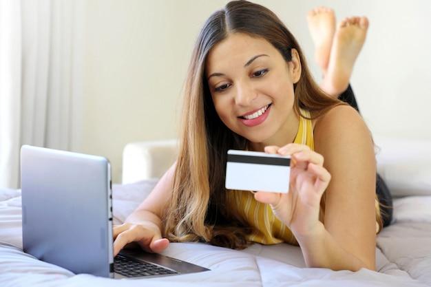Sorridente giovane donna rilassata sdraiata sul letto leggendo il suo numero di carta di credito e inserire il numero sul taccuino facendo acquisti online comodamente a casa