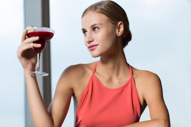 Sorridente giovane donna sollevare il bicchiere con cocktail