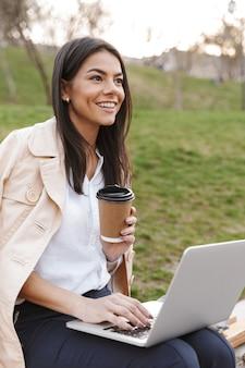 Sorridente giovane donna utilizzando il computer portatile