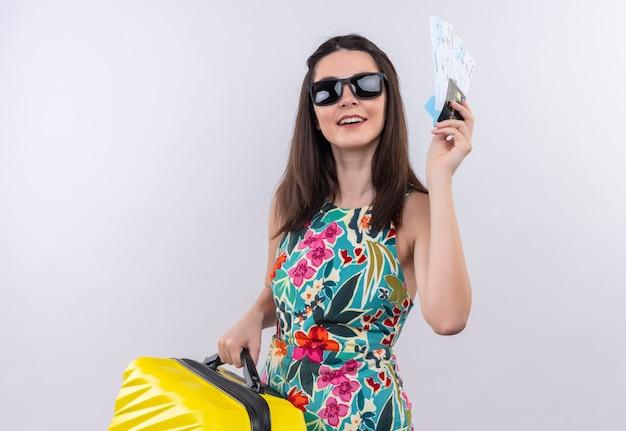 Sorridente giovane donna viaggiatore in abito multicolore con gli occhiali in possesso di una borsa mobile e biglietti sul muro bianco
