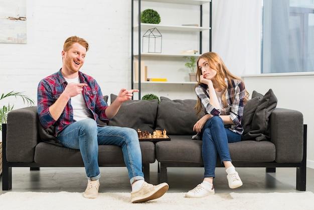 Sorridente giovane prendendo in giro la sua ragazza dopo aver vinto il gioco degli scacchi in salotto