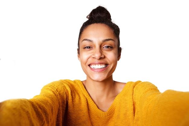 Sorridente giovane signora africana prendendo selfie