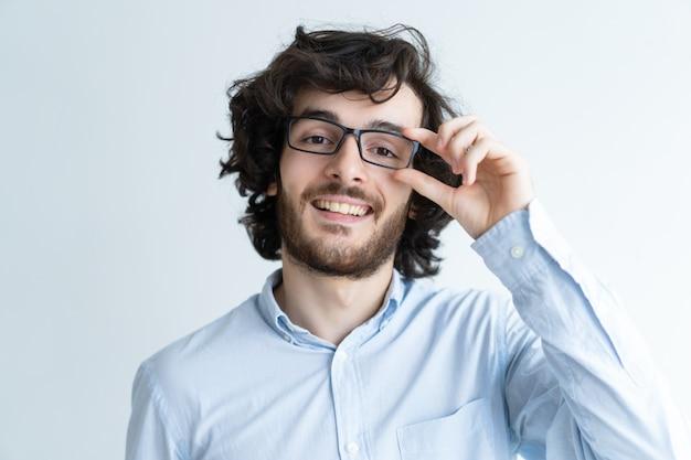 Sorridente giovane uomo dai capelli scuri, regolando gli occhiali
