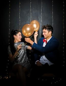 Sorridente giovane uomo e donna con palloncini sulla panchina
