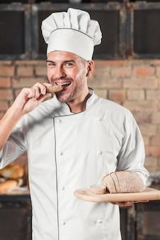 Sorridente giovane uomo mangiare una fetta di pane