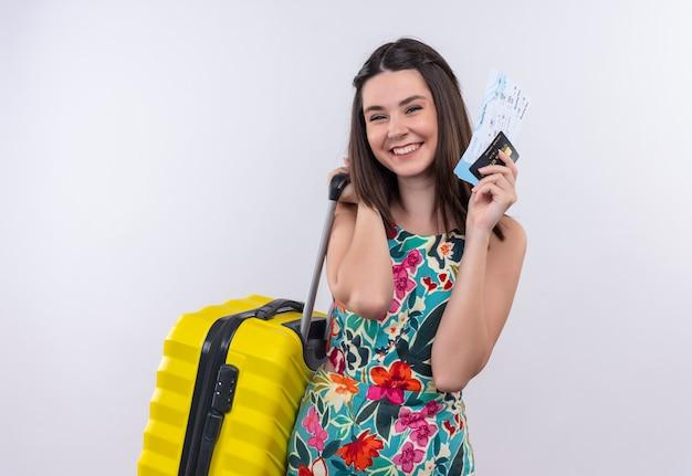 Sorridente giovane viaggiatore che indossa un abito multicolore in possesso di una borsa mobile e biglietti sul muro bianco