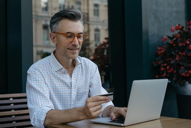 Sorridente imprenditore maturo tenendo la carta di credito