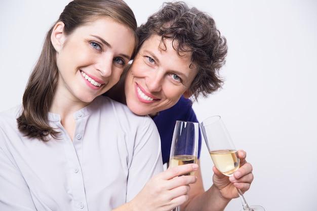 Sorridente madre e figlia tintinnio di champagne