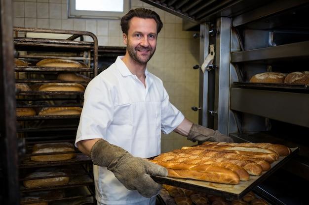 Sorridente panettiere rimozione di panini cotti dal forno