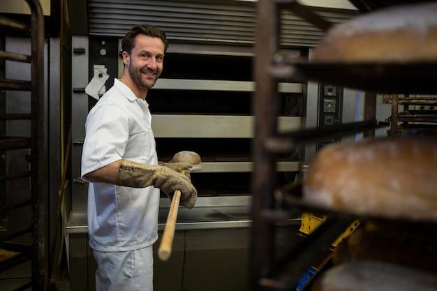 Sorridente panettiere rimozione panino sfornato dal forno