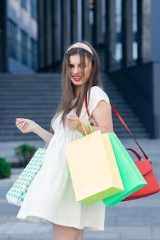 Sorridente ragazza adolescente con molte borse della spesa al centro commerciale. concetto di vendita al dettaglio, gesto e vendita.