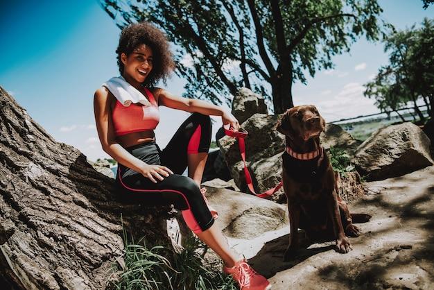 Sorridente ragazza africana con cane all'aperto