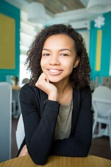 Sorridente ragazza afroamericana seduta in un bar