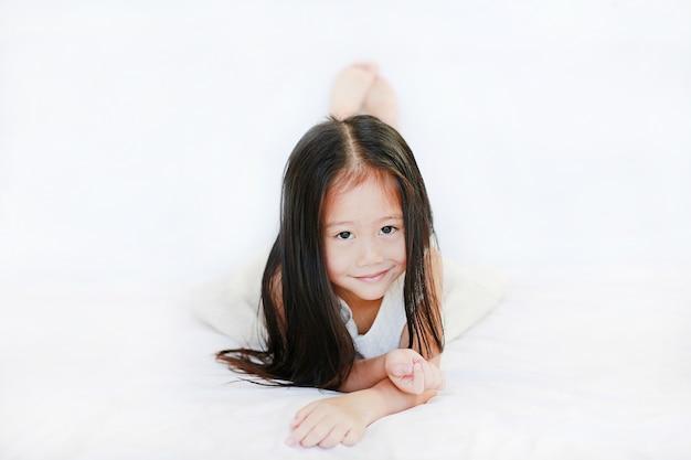 Sorridente ragazza asiatica carina sdraiata sul letto su sfondo bianco.