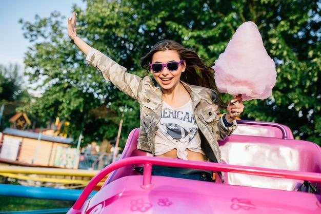 Sorridente ragazza attraente in occhiali da sole in sella a montagne russe per bambini
