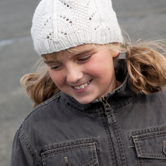 Sorridente ragazza bionda fuori in berretto di lana e giacca demin