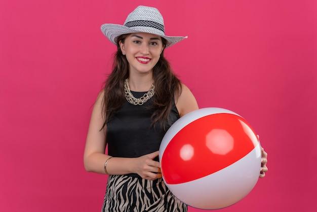 Sorridente ragazza del viaggiatore che indossa maglietta nera in cappello che tiene palla gonfiabile su sfondo rosso