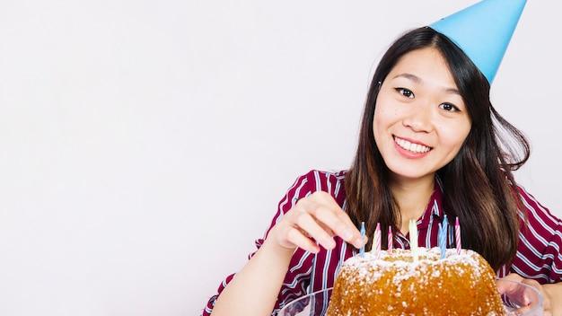 Sorridente ragazza di compleanno con gustosa torta
