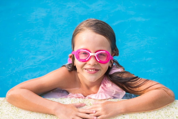 Sorridente ragazza felice in occhiali per nuotare in piscina all'aperto