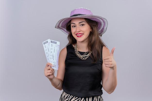 Sorridente ragazza giovane viaggiatore che indossa la maglietta nera in cappello che tiene la valigia e il suo pollice in alto su sfondo bianco