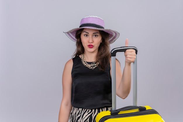 Sorridente ragazza giovane viaggiatore che indossa la maglietta nera in cappello il suo pollice in alto su sfondo bianco