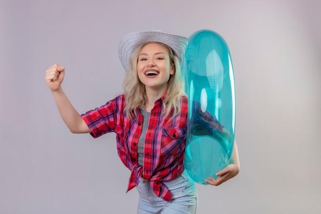 Sorridente ragazza giovane viaggiatore indossa la camicia rossa in cappello che tiene anello gonfiabile facendo un forte gesto su sfondo bianco isolato