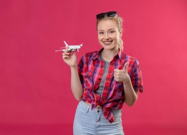 Sorridente ragazza giovane viaggiatore indossa una camicia rossa e bicchieri sulla sua testa tenendo il piano di giocattoli il suo pollice in alto su sfondo rosa isolato