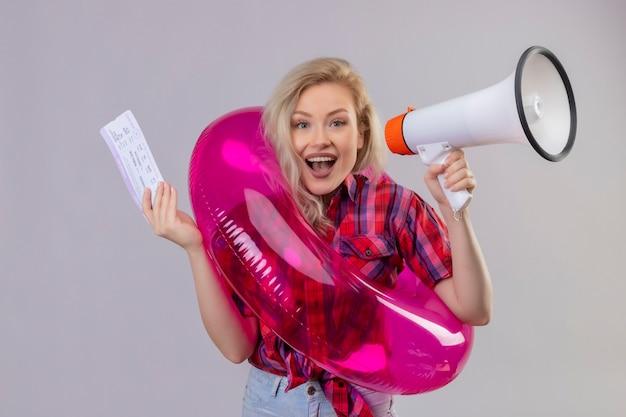 Sorridente ragazza giovane viaggiatore indossa una camicia rossa in anello gonfiabile tenendo l'altoparlante e il biglietto su sfondo bianco isolato