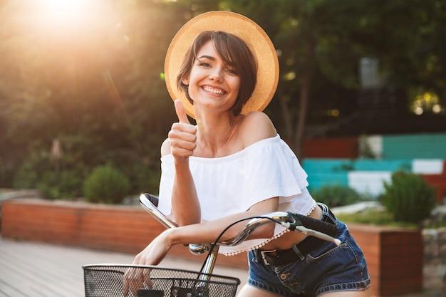 Sorridente ragazza in abiti estivi andare in bicicletta