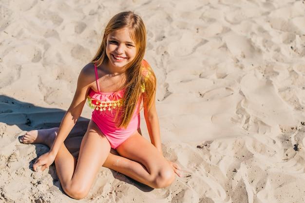 Sorridente ragazza magra seduto su morbida sabbia fine
