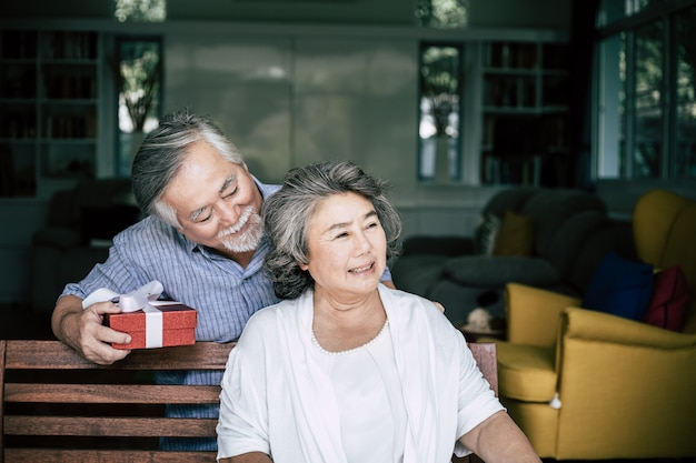 Sorridente senior marito facendo sorpresa dando regalo a sua moglie
