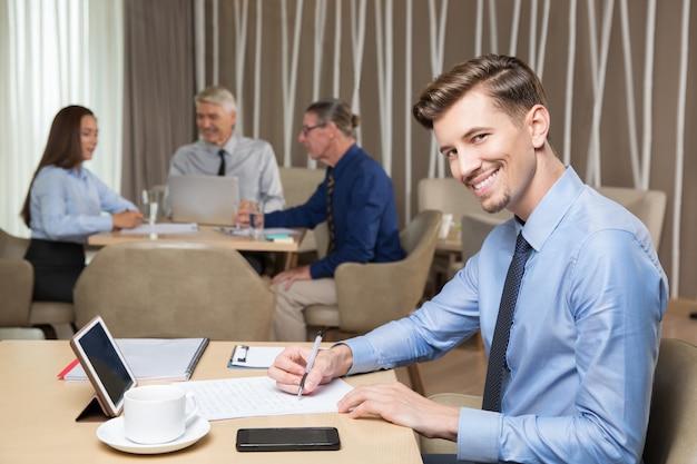 Sorridente successo giovane che lavora in cafe