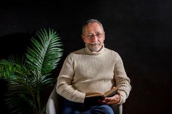 Sorridente uomo anziano con il libro