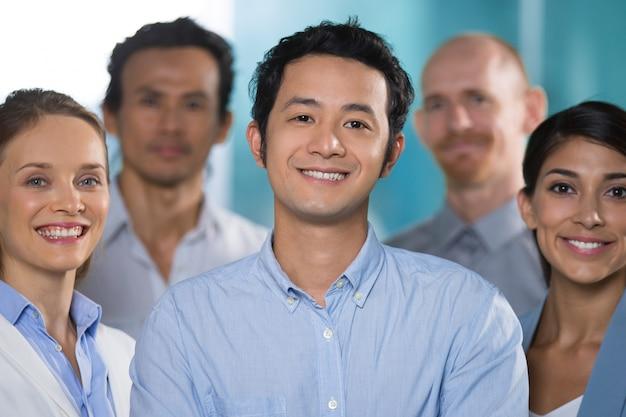 Sorridente uomo asiatico che lavora con i professionisti