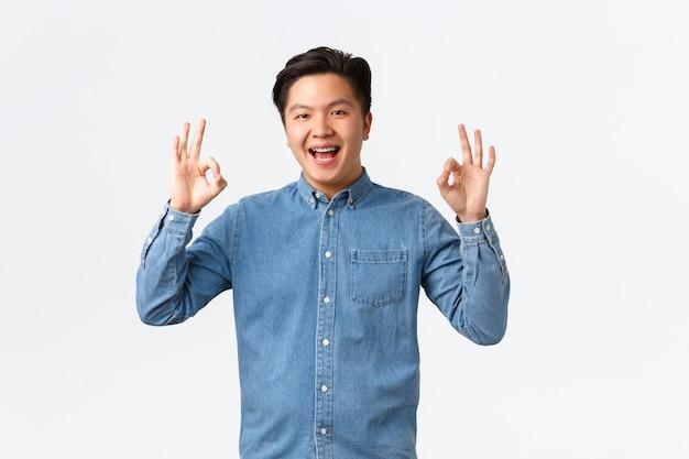 Sorridente uomo asiatico soddisfatto con le parentesi graffe in camicia blu, mostrando il gesto giusto, congratulandosi con la persona con un lavoro eccellente, ben fatto, consiglia un servizio perfetto o di qualità, muro bianco