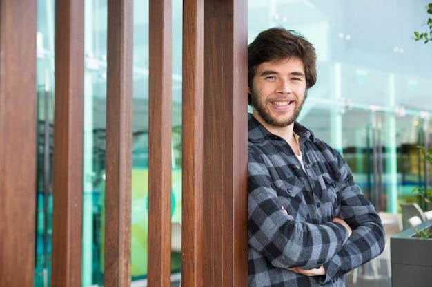 Sorridente uomo attraente in piedi all'aperto con le braccia incrociate