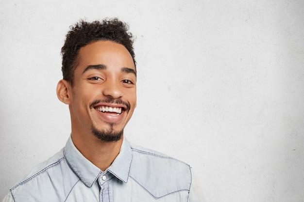 Sorridente uomo barbuto con viso ovale, acconciatura alla moda, essere contento