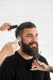 Sorridente uomo barbuto nel negozio di barbiere