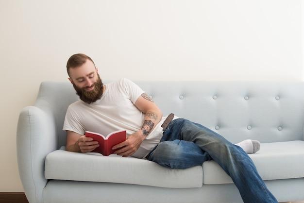 Sorridente uomo barbuto sdraiato sul divano e leggendo il libro