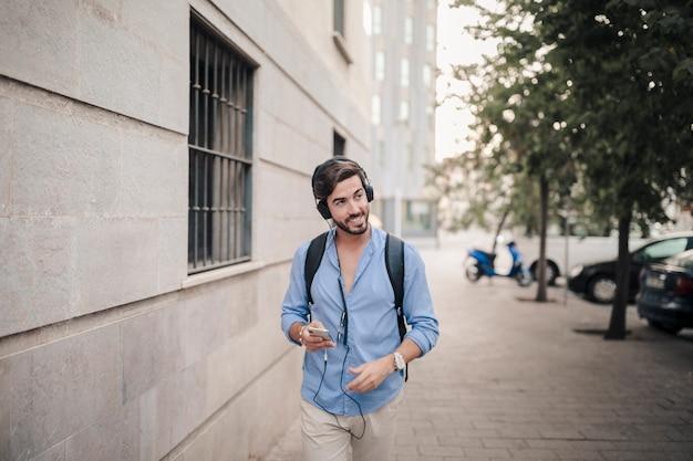 Sorridente uomo che cammina sul marciapiede ascoltando musica