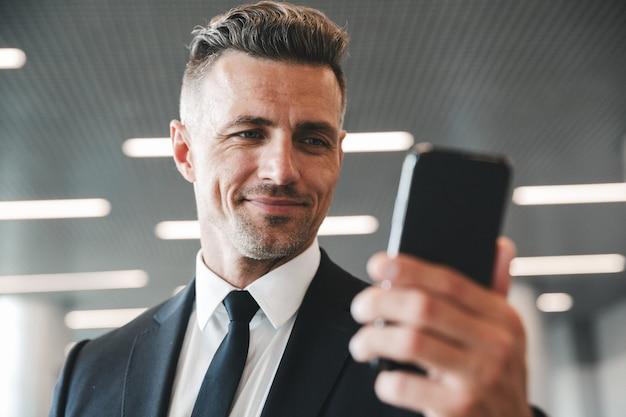 Sorridente uomo d'affari maturo guardando il telefono cellulare