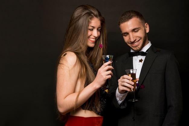 Sorridente uomo e donna con bicchieri di bevande e confetti