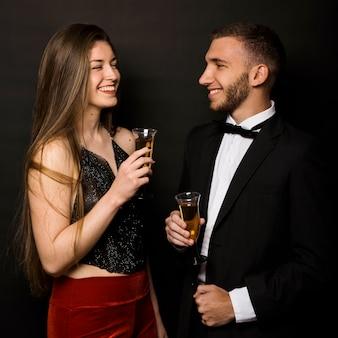 Sorridente uomo e donna in giacca da pranzo e abiti da sera con bicchieri di bevande