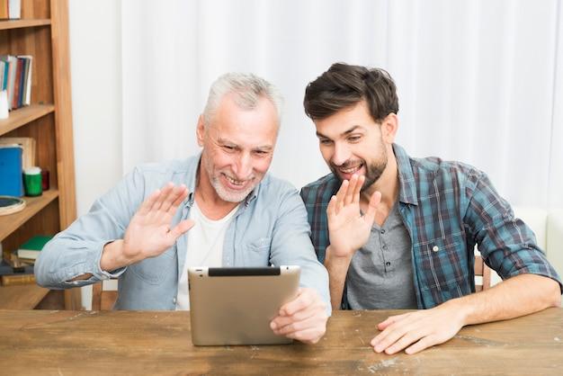 Sorridente uomo invecchiato e felice giovane ragazzo agitando le mani e utilizzando tablet al tavolo